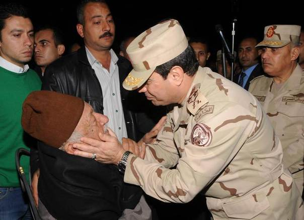 Egypt's Army Chief General Abdel Fattah al-Sisi (R) comforts the father of an officer who was killed yesterday morning in northern Sinai during a military funeral was held for 5 of the soldiers in Cairo, Egypt, early January 26, 2014. REUTERS/Egypt Ministry of Defence via Al Youm Al Saabi Newspaper