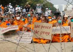 Buddhist monks pray and hold placards behind a wire barricade at Dhammakaya temple
