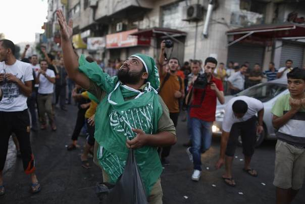 A Palestinian throws sweets as others celebrate what they said was a victory over Israel, following a ceasefire in Gaza City August 26, 2014. REUTERS/Suhaib Salem