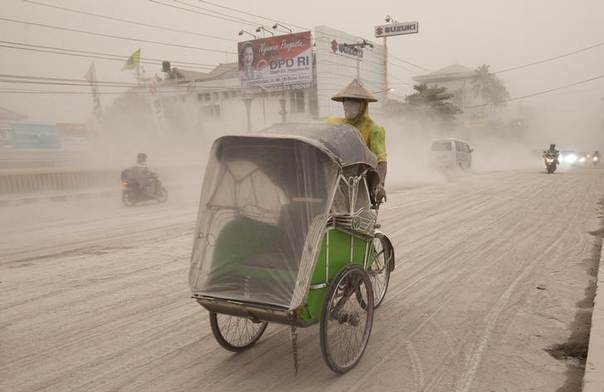A man wears a mask as he rides a becak, a kind of rickshaw, on a road covered with from Mount Kelud, in Yogyakarta February 14, 2014 REUTERS/Dwi Oblo