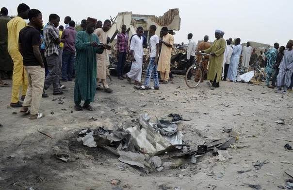 A man takes a picture of a crater after an explosion of one of two vehicles laden with explosives in Ajilari-Gomari near the city's airport, in Maiduguri, Nigeria, March 2, 2014. REUTERS/Stringer