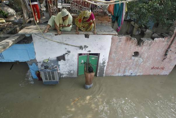 A man unlocks the door of his flooded house as other residents watch after a rise in the water level of the Yamuna river in New Delhi, June 19, 2013. REUTERS/Anindito Mukherjee