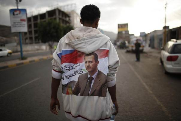 A protester loyal to the Shi'ite Muslim Al-Houthi group, also known as Ansarullah, walks with a poster of Syria's President Bashar al-Assad attached to his back during a demonstration against potential strikes on the Syrian government, in Sanaa August 30, 2013. The poster reads,