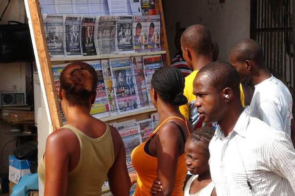 People read news headlines at a newsstand in Conakry March 28, 2014. Picture taken March 28, 2014. REUTERS/Saliou Samb