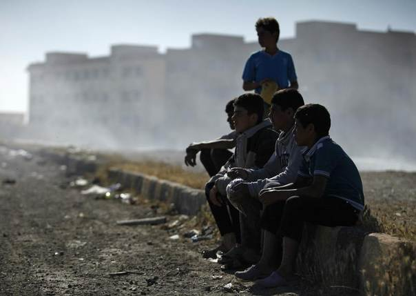 A group of boys watch activists sing and shout slogans against Syrian president Bashar al-Assad in Raqqa province, eastern Syria, April 25, 2013. REUTERS/Nour Kelze