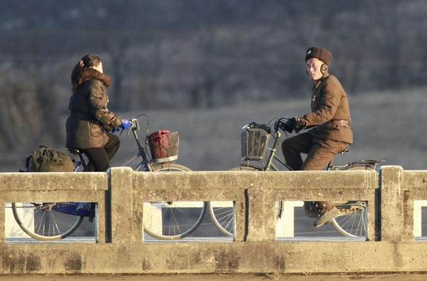 A North Korean soldier (R) and a resident ride bicycles past a bridge on the banks of Yalu River, about 100 km (62 miles) from the North Korean town of Sinuiju, opposite the Chinese border city of Dandong, December 14, 2013. REUTERS/Jacky Chen