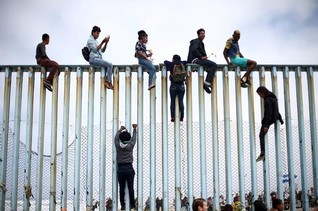 Members of a caravan of migrants from Central America climb up the border fence