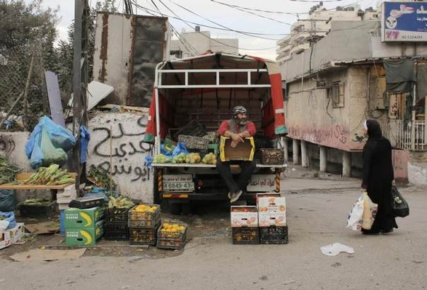 A Palestinian vendor sells fruits and vegetables from the back of a van in the Shuafat refugee camp in the West Bank near Jerusalem November 25, 2013. REUTERS/Ammar Awad