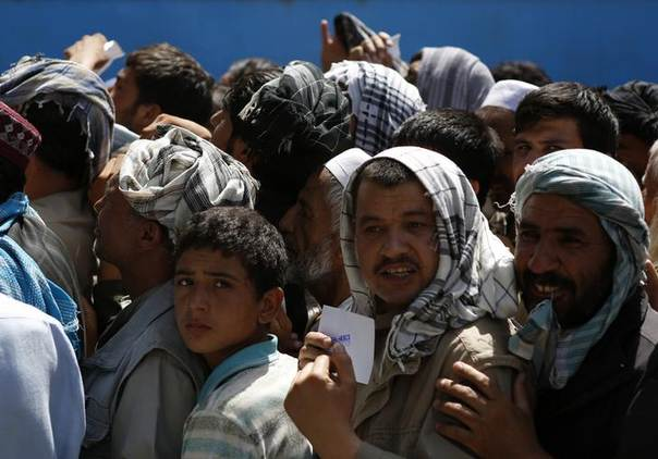 Afghan men line up to receive aid from the Afghanistan Chamber of Commerce and Industries (ACCI) during the month of Ramadan in Kabul August 1, 2013. REUTERS/Mohammad Ismail