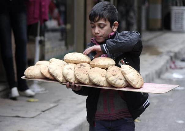 A boy sells bread in Aleppo's Bustan al-Qasr neighbourhood December 26, 2013. REUTERS/Houssam Al-Halabi