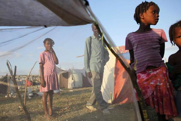 Earthquake survivors stand next to a makeshift tent at the Cite Soleil in Port-au-Prince, February 2010. REUTERS/Eliana Aponte