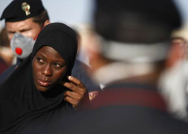 A migrant woman is seen next to Italian policemen as she disembarks from a navy ship in the Sicilian harbour of Pozzallo June 30, 2014. REUTERS/Antonio Parrinello