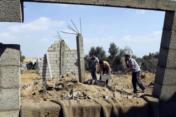 Palestinians inspect what police said is the aftermath of an Israeli air strike in Khan Younis in the southern Gaza Strip July 6, 2014. REUTERS/Ibraheem Abu Mustafa