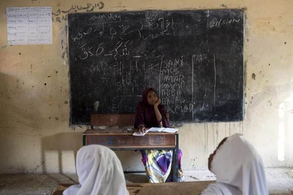 A teacher watches as students recite Quranic verses at an Islamic school in Maiduguri, Nigeria, May 24, 2014. REUTERS/Joe Penney