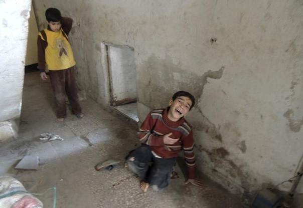 A wounded boy reacts at a site hit by what activists said was shelling by forces loyal to Syria's President Bashar al-Assad in Arbeen, in the eastern Damascus suburb of Ghouta March 22, 2014. REUTERS/Diaa Al-Din