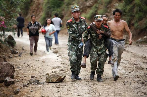 Paramilitary policemen evacuate an injured man after a deadly earthquake hit Longtoushan town, Ludian county, Zhaotong, Yunnan province, China, August 3, 2014. REUTERS/China Daily