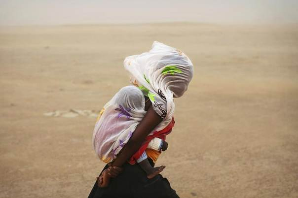 A woman carrying her baby and wrapped with a shawl walks through a sandstorm in Timbuktu July 29, 2013. REUTERS/Joe Penney