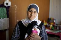 Syrian refugee Omayma al Hushan poses with her favorite toy