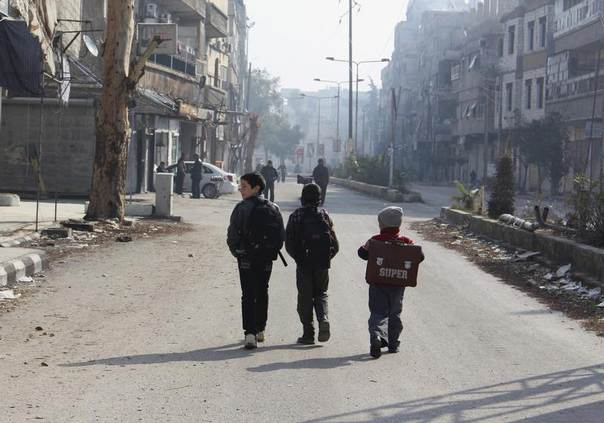 Boys walk to school in the Damascus suburb of Arbeen January 1, 2014. REUTERS/Bassam Al-Erbeeni