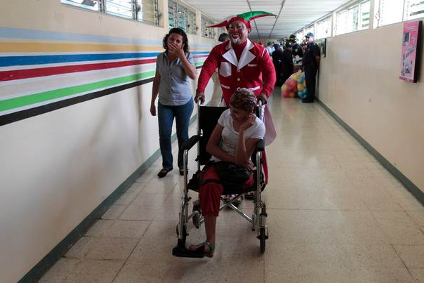 A clown pushes the wheelchair of a cancer patient at the La