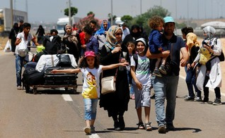 Syrians, who say they are returning to Syria ahead of the Eid al-Fitr, carry their belongings as they walk to the Turkish Cilvegozu border gate