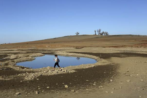 A visitor walks near receding waters at Folsom Lake, which is at 17 pct of its capacity, amid drought in California, Jan. 22, 2014. REUTERS/Robert Galbraith