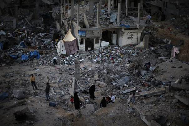 Palestinians sit atop the ruins of their house which witnesses said was destroyed during the Israeli offensive, in the east of Gaza City September 3, 2014.  REUTERS/Suhaib Salem