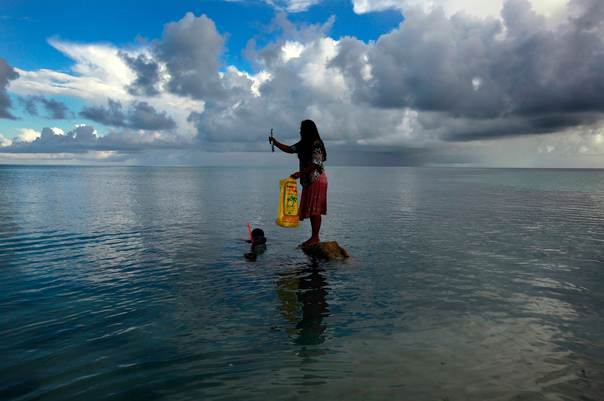 Binata Pinata stands on top of a rock holding a fish her husband Kaibakia just caught off Bikeman islet, located off South Tarawa in the central Pacific island nation of Kiribati on May 25, 2013. REUTERS/David Gray