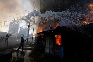 People try to put out a fire at properties set ablaze by rioters in Kawangware slums in Nairobi, Kenya
