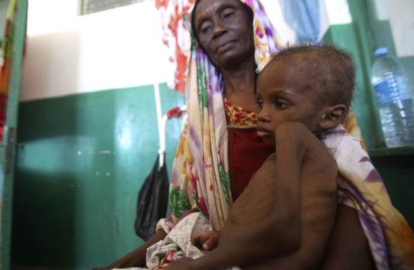 A Somali woman holds a malnourished child as they wait for medical attention at the paediatric ward of Banadir hospital in Mogadishu, April 28, 2014. REUTERS/Ismail Taxta
