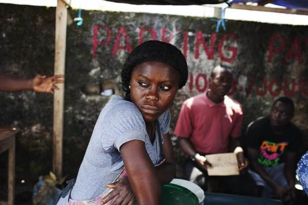A woman selling food at a stall gazes at people at the bus station she works at in Douala, Cameroon, November 4, 2013. REUTERS/Joe Penney