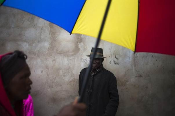 A woman holding an umbrella walks past a man taking shelter from the rain while waiting outside a mobile social security office near Qunu, in South Africa's Eastern Cape Province, Dec. 11, 2013. REUTERS/Adrees Latif