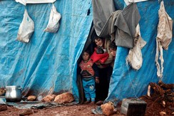 Displaced Syrian children look out from their tents at Kelbit refugee camp, near the Syrian-Turkish border, in Idlib province, Syria