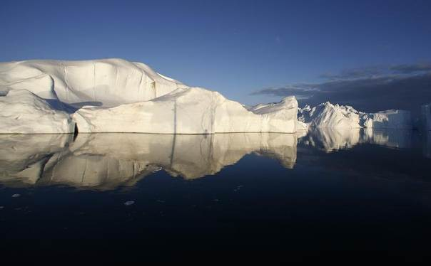 Icebergs are reflected in waters at the mouth of the Jakobshavn ice fjord near Ilulissat in Greenland in this photo taken May 15, 2007. REUTERS/Bob Strong/Files