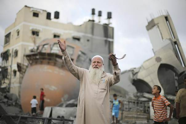 A Palestinian man reacts in front of the remains of a mosque, which witnesses said was destroyed in an Israeli air strike before a 72-hour truce, in Khan Younis in the southern Gaza Strip August 11, 2014. REUTERS/Ibraheem Abu Mustafa