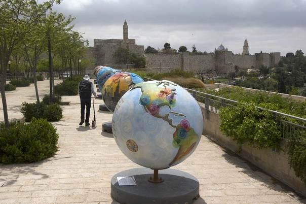 A man walks near giant globes on display outside the walls of Jerusalem's Old City, April 17, 2013. The exhibit, by non-profit group Cool Globes which aims to raise awareness of climate change, will be on display through the summer. REUTERS/Ronen Zvulun