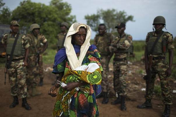 The relative of a woman that recently gave birth yesterday to twins holds one of the babies before departing towards Chad's border, escorted by troops from the African Union operation in CAR (MISCA) in the northern town of Kaga Bandoro April 29, 2014. REUTERS/Siegfried Modola