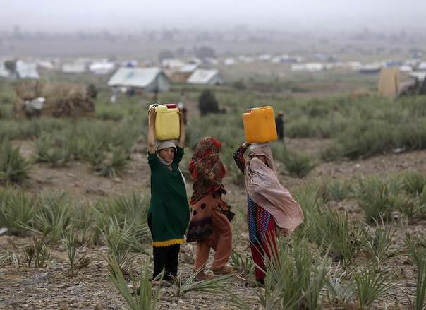 Displaced Pakistani girls carry drinking water on their heads at a refugee camp in Khost province July 2, 2014. REUTERS/Omar Sobhani