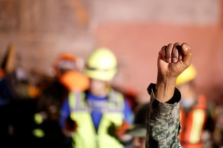 A Mexican soldier gestures to ask for silence his team search for survivors after an earthquake in Mexico City