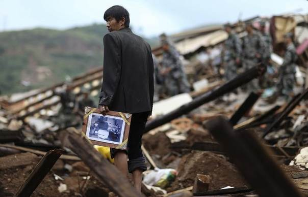 A man holds a picture as he stands among debris of collapsed buildings after an earthquake hit Longtoushan township of Ludian county, Yunnan province August 4, 2014. REUTERS/Wong Campion