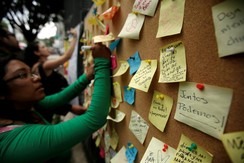 A woman writes a message on a board next to other encouraging messages, after an earthquake in Mexico City, Mexico September 27, 2017