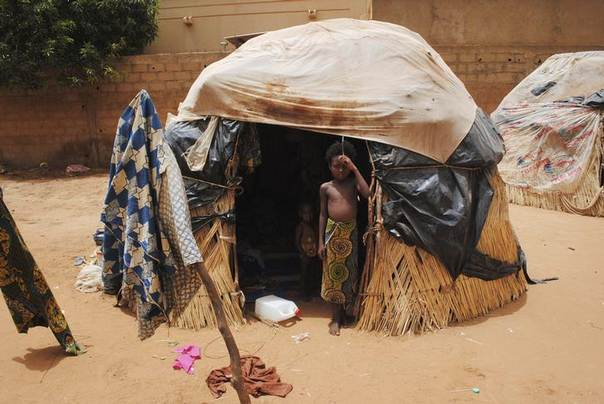 A girl stands outside a hut in Niger's capital Niamey in the Sahel region.  Picture taken June 10, 2012. REUTERS/Richard Valdmanis