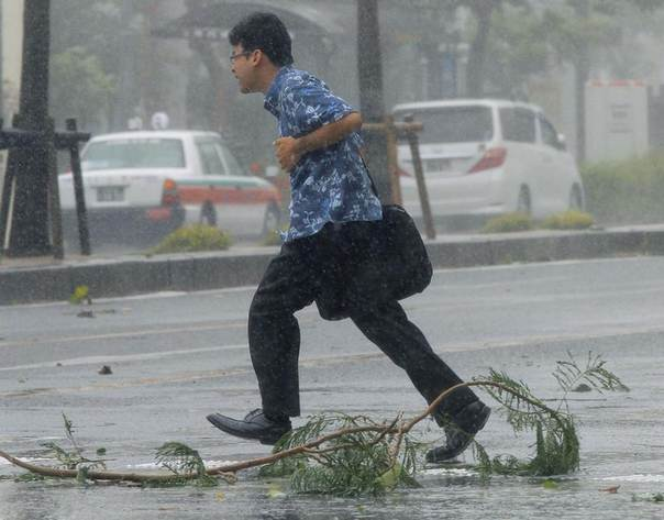 A man walks across a road at a pedestrian crossing amid strong winds caused by Typhoon Neoguri in Naha, on Japan's southern island of Okinawa, in this photo taken by Kyodo, July 8, 2014. REUTERS/Kyodo