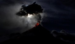 The super blue moon illuminates Mayon Volcano as it spews lava during a mild eruption, hours after a total lunar eclipse in Legazpi