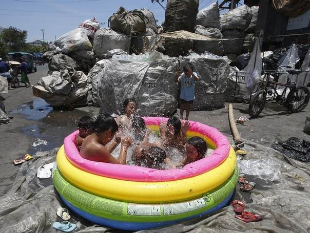 Philippine children living in a squatters area play in an inflatable pool to cool themselves from the summer heat in Tondo, Manila, April 30, 2013. REUTERS/Erik De Castro