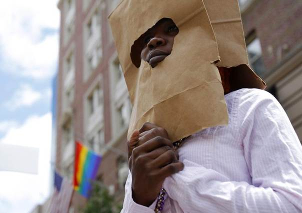 An asylum seeker from Uganda covers her face with a paper bag in order to protect her identity as she marches with the LGBT Asylum Support Task Force during the Gay Pride Parade in Boston, Massachusetts June 8, 2013. REUTERS/Jessica Rinaldi