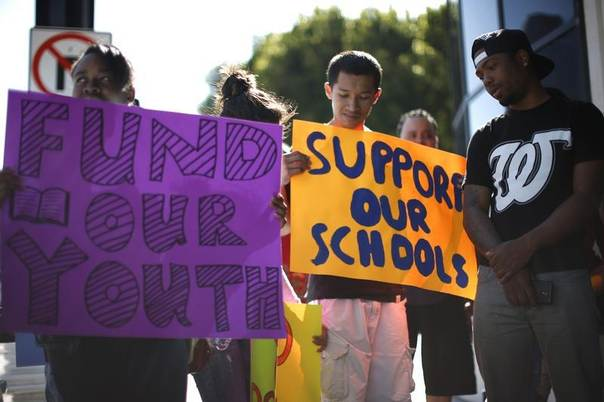 People hold signs during a protest outside the Los Angeles Unified School District, calling for more investment in the highest-need schools in Los Angeles, California, April 7, 2014. REUTERS/Lucy Nicholson