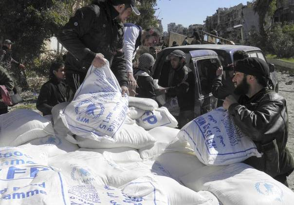 Men unload bags of humanitarian aid at a besieged area of Homs February 12, 2014 REUTERS/Thaer Al Khalidiya