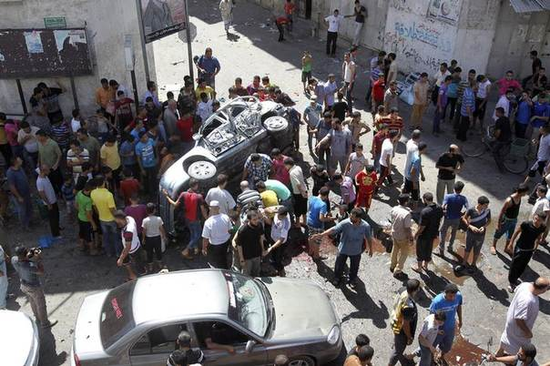 Palestinians surround a wreckage of a car which witnesses said was hit by an Israeli air strike, in Gaza City August 25, 2014. REUTERS/Ahmed Zakot