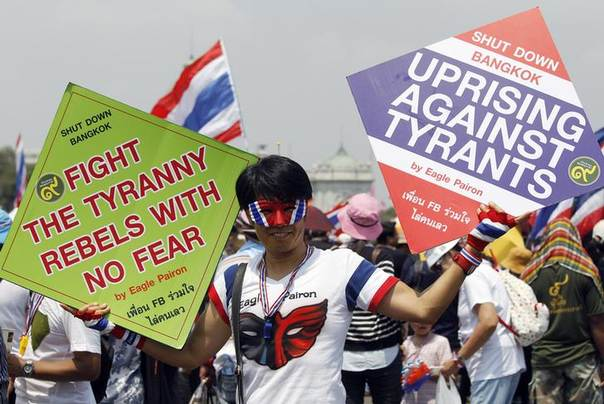 An anti-government protester holds placards during a rally at the Royal Plaza near Government House in Bangkok March 29, 2014 REUTERS/Chaiwat Subprasom